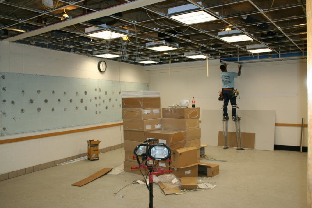 A contractor installs new ceiling grids
